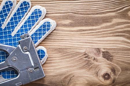 staple gun: Set of staple gun protective gloves on wooden board. Stock Photo