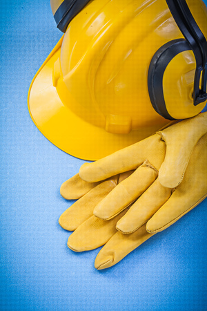 ear muffs: Noise reduction ear muffs safety gloves hard hat on blue background construction concept.