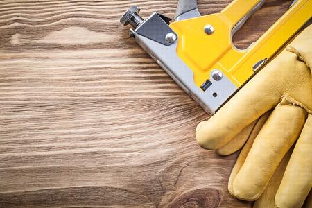 staple gun: Stapler gun safety gloves on wood board construction concept.