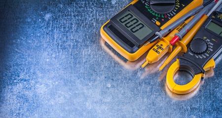 the tester: Digital ammeter electric tester multimeter on metallic background.