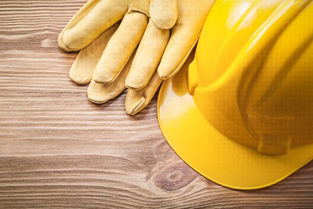 Yellow hard hat protective gloves on wooden board construction concept.