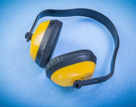 ear muffs: Protective ear muffs on blue background construction concept.