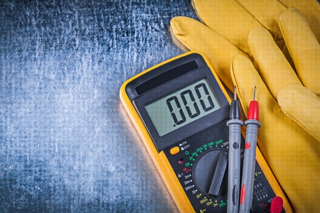 the tester: Digital electric tester test leads protective gloves on metallic background.