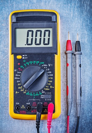 the tester: Digital electrical tester on metallic surface top view.