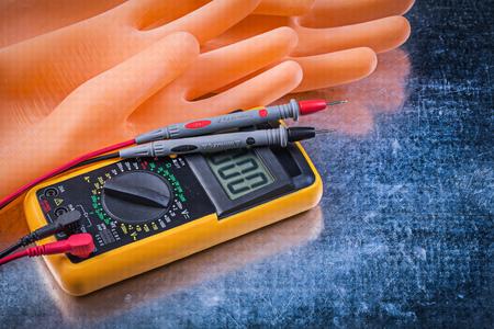 Digitale elektrische tester elektriciens rubberhandschoenen op metalen achtergrond. Stockfoto