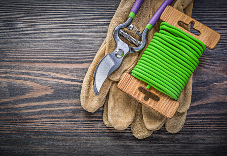 pruning shears: Pruning shears safety gloves garden tie wire on wood board gardening concept. Stock Photo