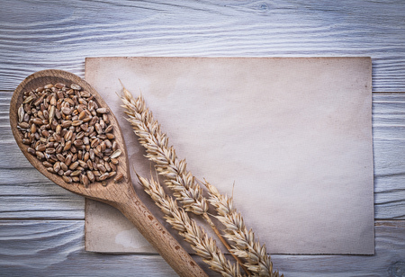 the ears of corn: Wheat rye ears corn crop wooden spoon vintage paper sheet on wood board food and drink concept. Stock Photo