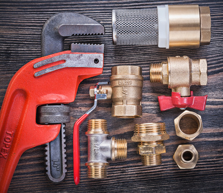 pipe wrench: Pipe wrench check valve with strainer filter brass connectors on wooden board. Stock Photo