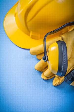 Earmuffs: Earmuffs protective gloves building helmet on blue background construction concept. Stock Photo