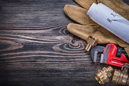 home safety: Working gloves pipe wrench engineering drawings brass plumbing fittings on wooden board copy space. Stock Photo