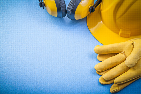 ear muffs: Ear muffs leather safety gloves building helmet on blue background construction concept.