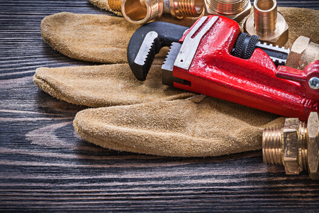 stainless steel range: Leather safety gloves pipe wrench brass plumbing connectors on wooden board. Stock Photo