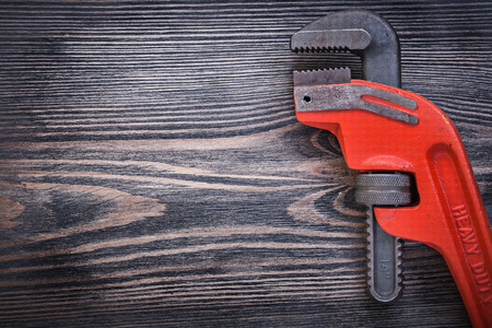 pipe wrench: Adjustable pipe wrench on wooden board copy space plumbing concept.