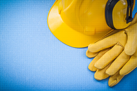 Earmuffs: Noise reduction earmuffs protective gloves hard hat on blue background construction concept.