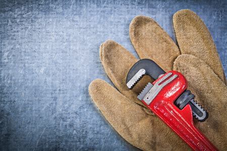 pipe wrench: Pipe wrench safety gloves on scratched metallic background. Stock Photo
