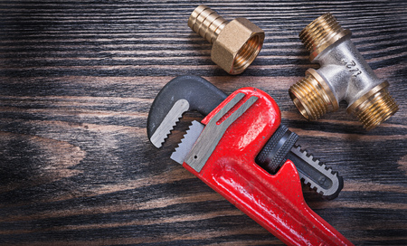Pipe wrench brass equal tee nipple hose connector on wooden background plumbing concept.