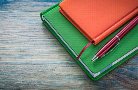 biro: Assortment of notepads biro pen on wooden board office concept.