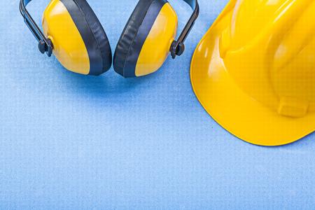 Earmuffs: Noise reduction earmuffs building helmet on blue background construction concept.
