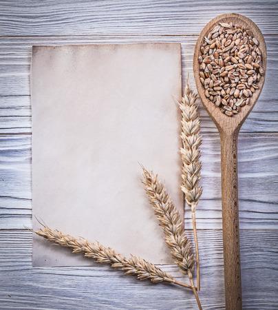the ears of corn: Ripe wheat rye ears corn wooden spoon clean vintage paper sheet on wood board directly above. Stock Photo