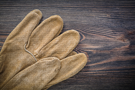 protective gloves: Pair of leather protective gloves on vintage wooden board agriculture concept.