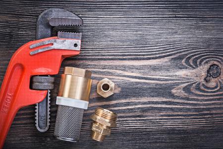 pezones: válvula de retención de llave de tubo con boquilla para manguera de filtro colador sobre tabla de madera.