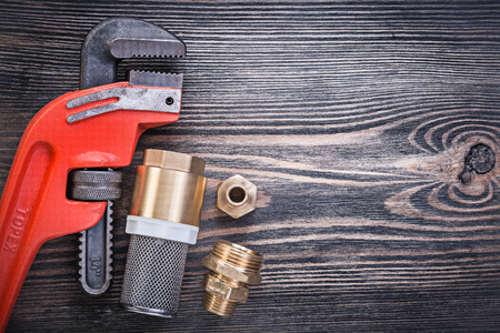 niples: v�lvula de retenci�n de llave de tubo con boquilla para manguera de filtro colador sobre tabla de madera.