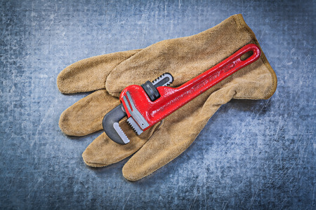 stainless steel range: Monkey wrench leather protective gloves on scratched metallic background plumbing concept. Stock Photo