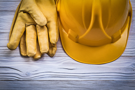 protective gloves: Protective gloves hard hat on wooden board construction concept.