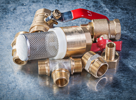 stainless steel range: Brass nipple hose connectors lever ball valve with strainer filter on metallic background plumbing concept. Stock Photo