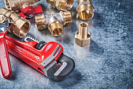 pipework: Assortment of plumbing brass hardware on metallic background construction concept.