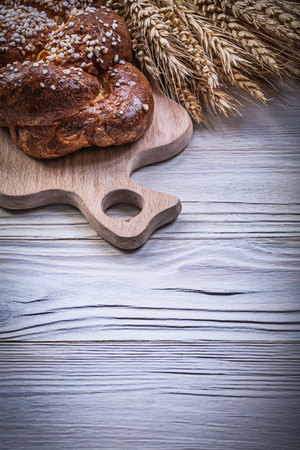long loaf: Carving board wheat rye ears long loaf on wooden background.