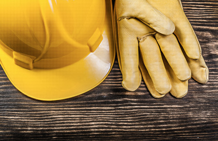 building safety: Safety gloves building helmet on wooden board construction concept.