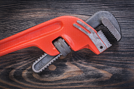 pipe wrench: Red metal pipe wrench on wooden board plumbing concept.