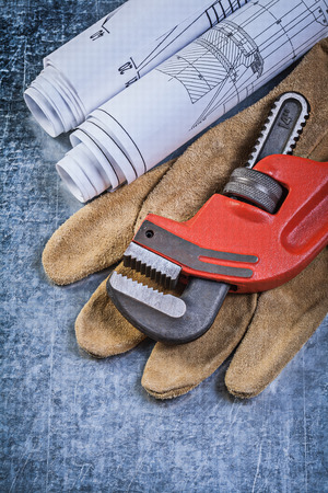 stainless steel range: Monkey wrench construction plans leather protective gloves on scratched metallic background. Stock Photo