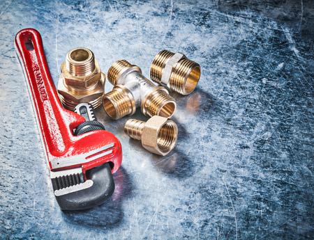 pezones: Llave de tubo conectores de manguera de lat�n en concepto de fontaner�a fondo met�lico rayado. Foto de archivo