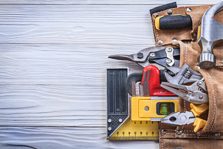implements: Leather toolbelt with building implements on wooden board copy space construction concept. Stock Photo
