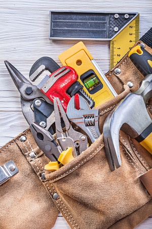 implements: Building implements in toolbelt on wooden board construction concept. Stock Photo