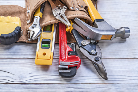 tape line: Tool belt pliers construction level tape line claw hammer pipe wrench adjustable spanner. Stock Photo