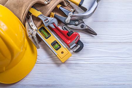 Lederen tool veiligheidsgordel bouwhelm op bouwconcept houten raad.