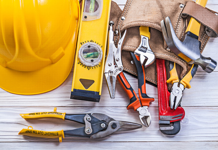 implements: Composition of building implements leather tool belt building helmet on wooden board. Stock Photo