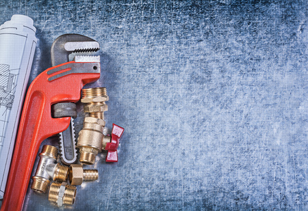 pipework: Monkey wrench blueprints brass gate valve hose nipples on metallic background copy space plumbing concept. Stock Photo