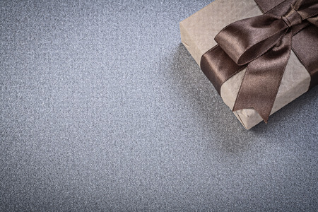 wrapped gift: Wrapped gift box on grey background celebrations concept.