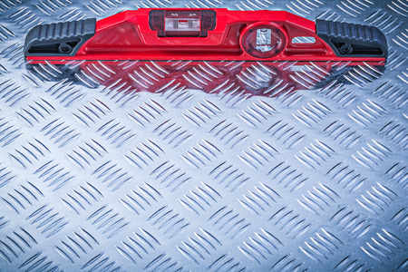 fluted: Red construction level on fluted metal plate maintenance concept.