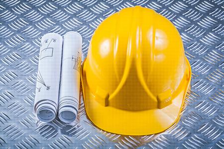 grooved: Rolled blueprints hard hat on grooved metal sheet construction concept.