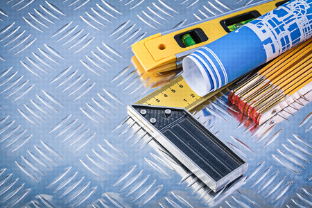 grooved: Construction level wooden meter blue rolled blueprints try square on grooved metal plate. Stock Photo