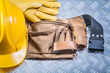 grooved: Leather building belt safety gloves hard hat on grooved metal plate construction concept.