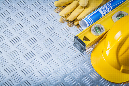 fluted: Blue blueprints hard hat protective gloves construction level on fluted metal plate.