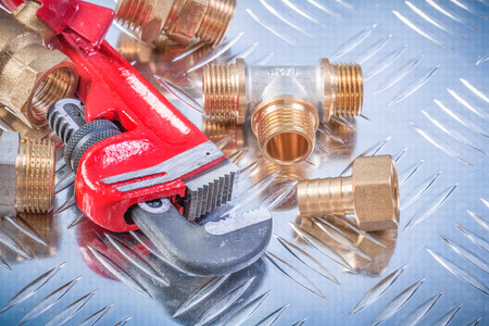 Collection of brass hardware on grooved metal background plumbing concept. Stock Photo