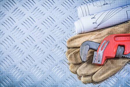 channeled: Monkey wrench blueprints safety gloves on grooved metal background construction concept.