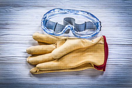 work gloves: Composition of safety workwear on wooden board construction concept.